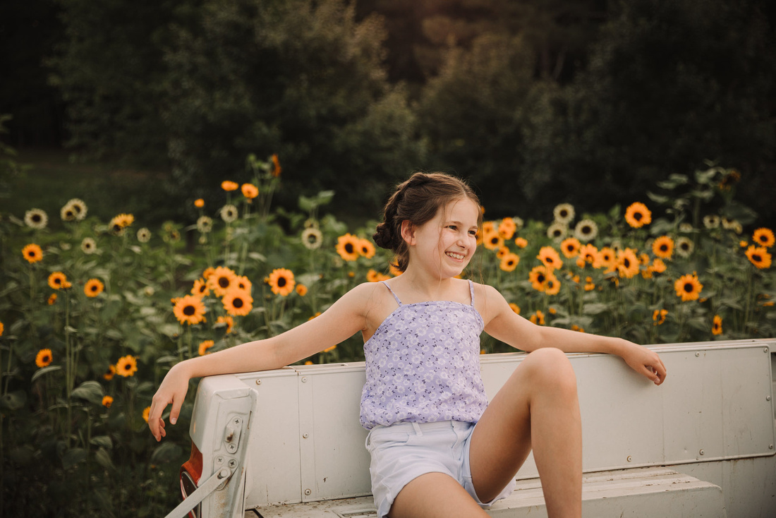 tween girl laughs in the bed of a old truck with sunflowers behind her during a photo session