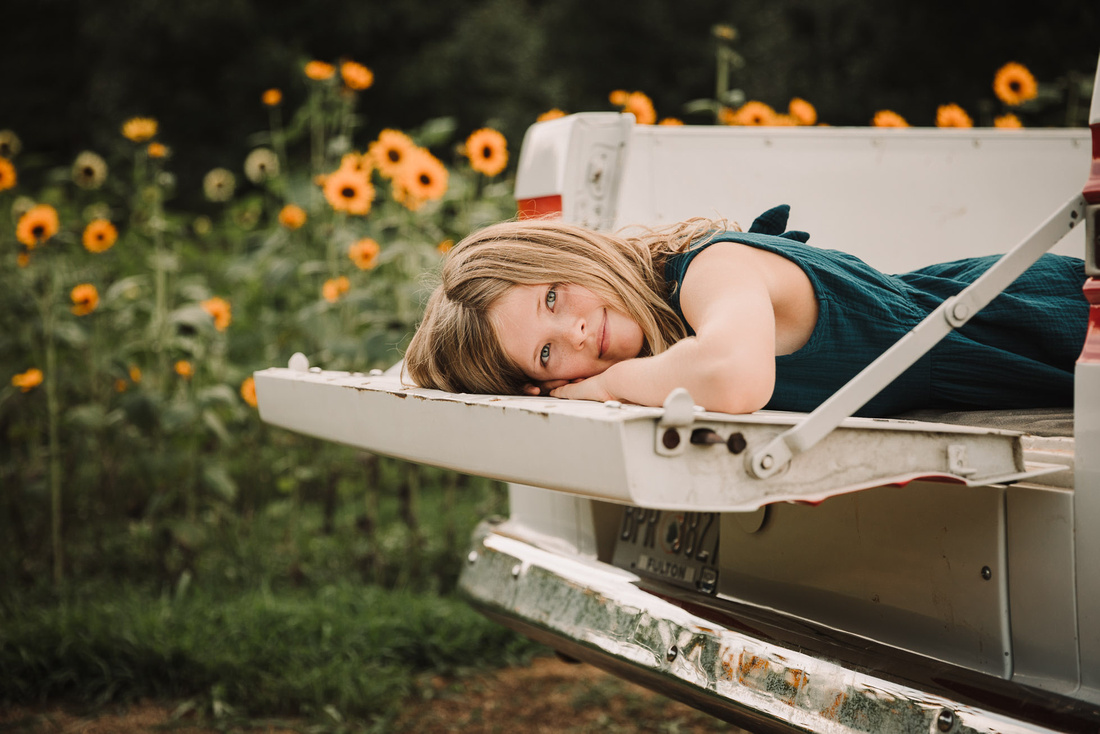 blonde girl laying in a truck bed with sunflowers in the background