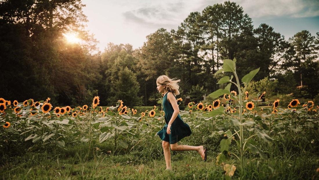 blonde girl running through a sunflower field at sunset