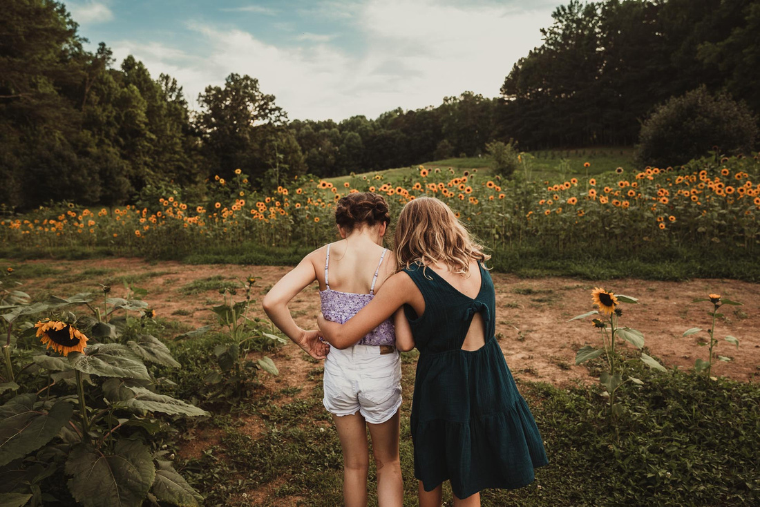 two girls walking away from the camera and towrds a field of sunflowers with their arms wrapped around each other