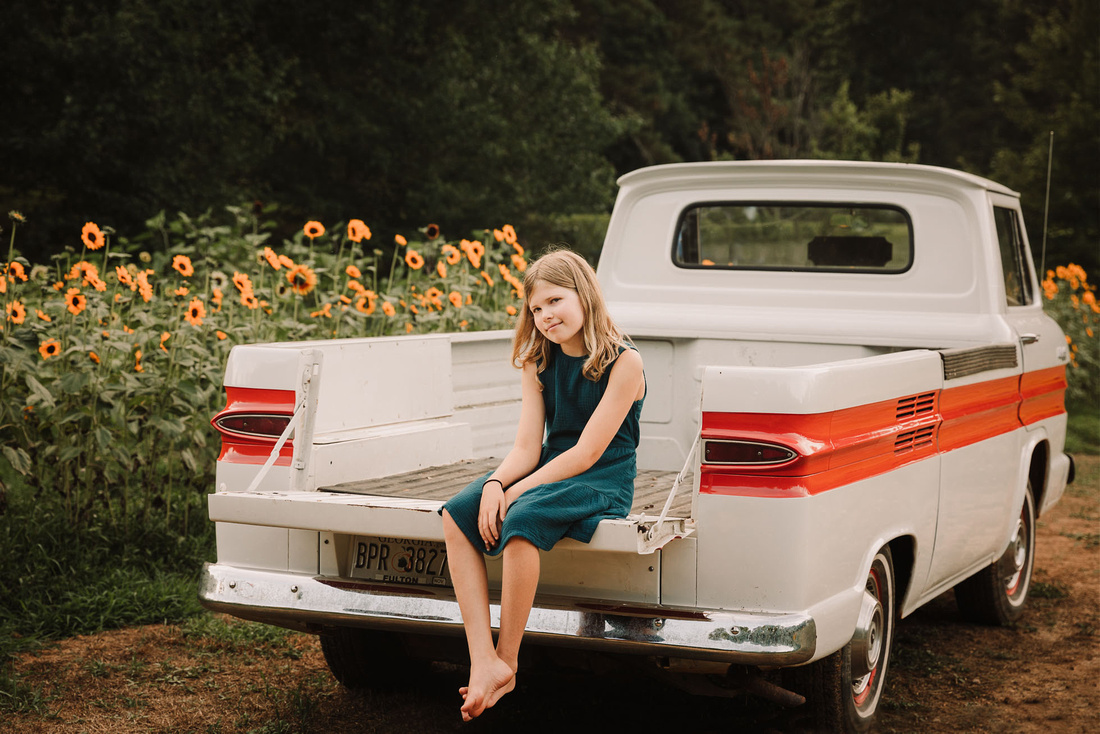 blonde little girl smiling and sitting in a pick up truck that is parked in front of sunflower field