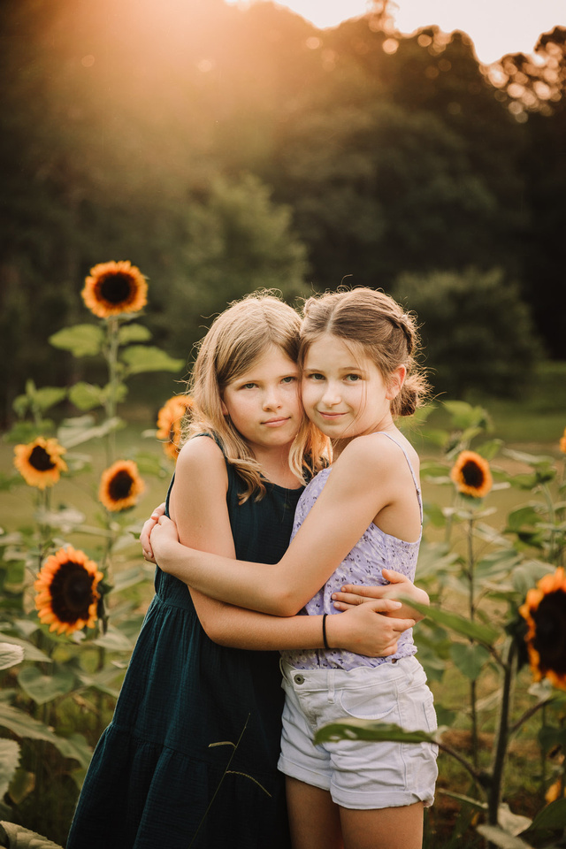 sisters hugging amoung sunflowers at sunset in Milton, GA