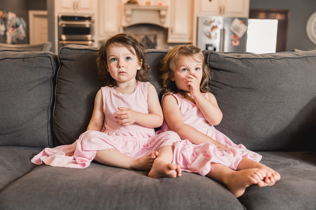 twin preschool sisters sitting on a couch in their living room during a family photo session