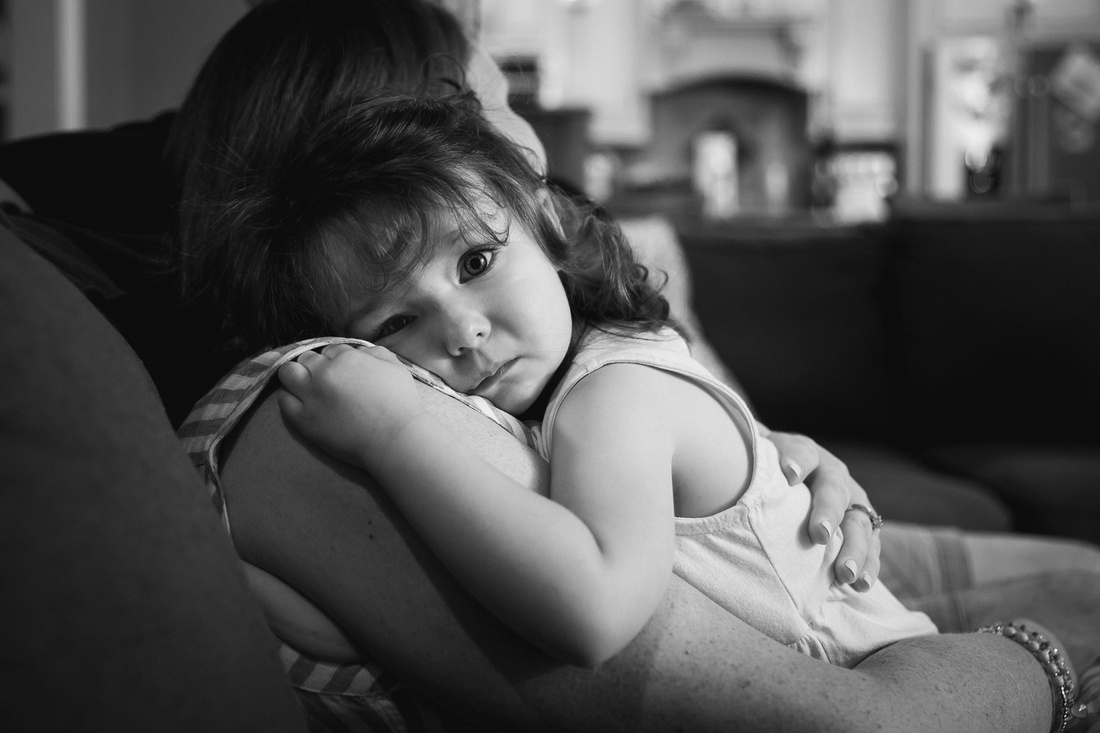 sad face of little girl being comforted by her mom