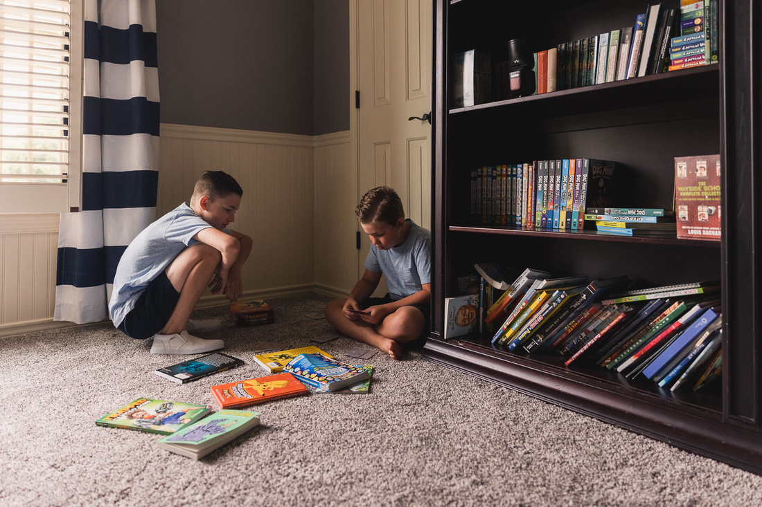 young brothers playing games on the floor of a bedroom during home photo session
