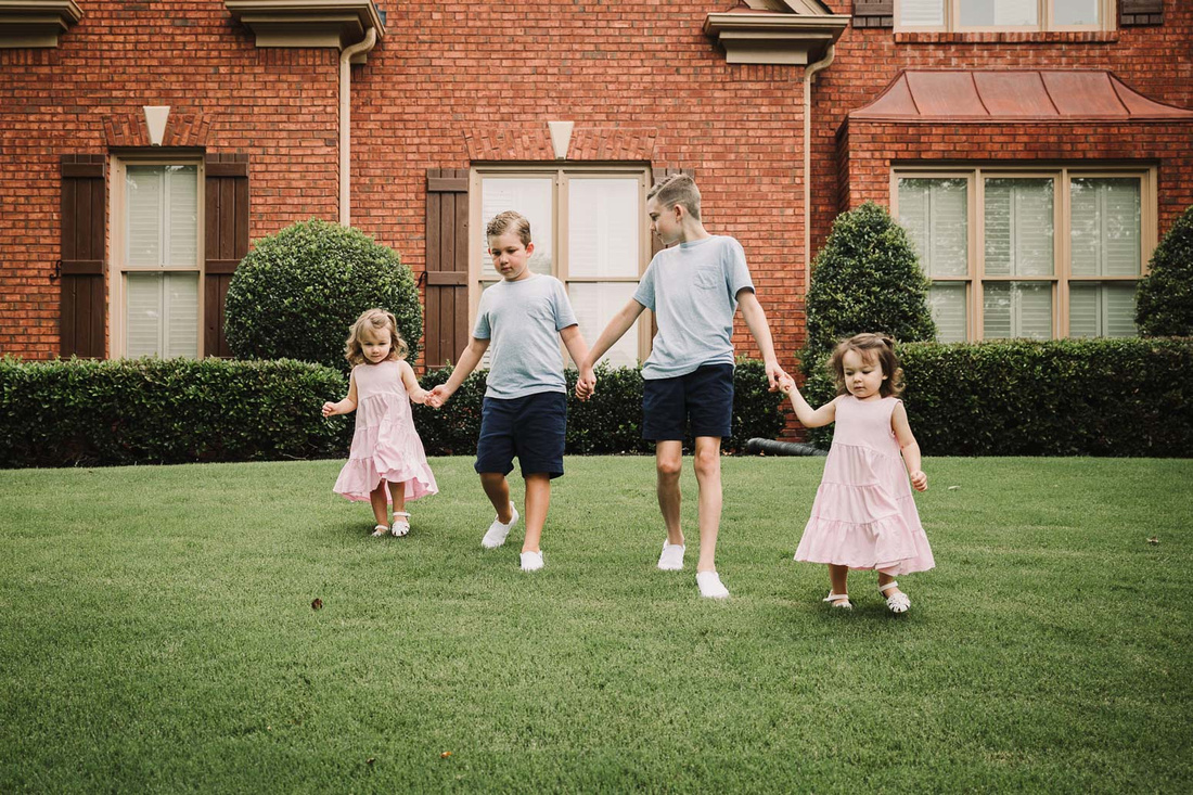 four siblings walking in front of their house by monica carlson