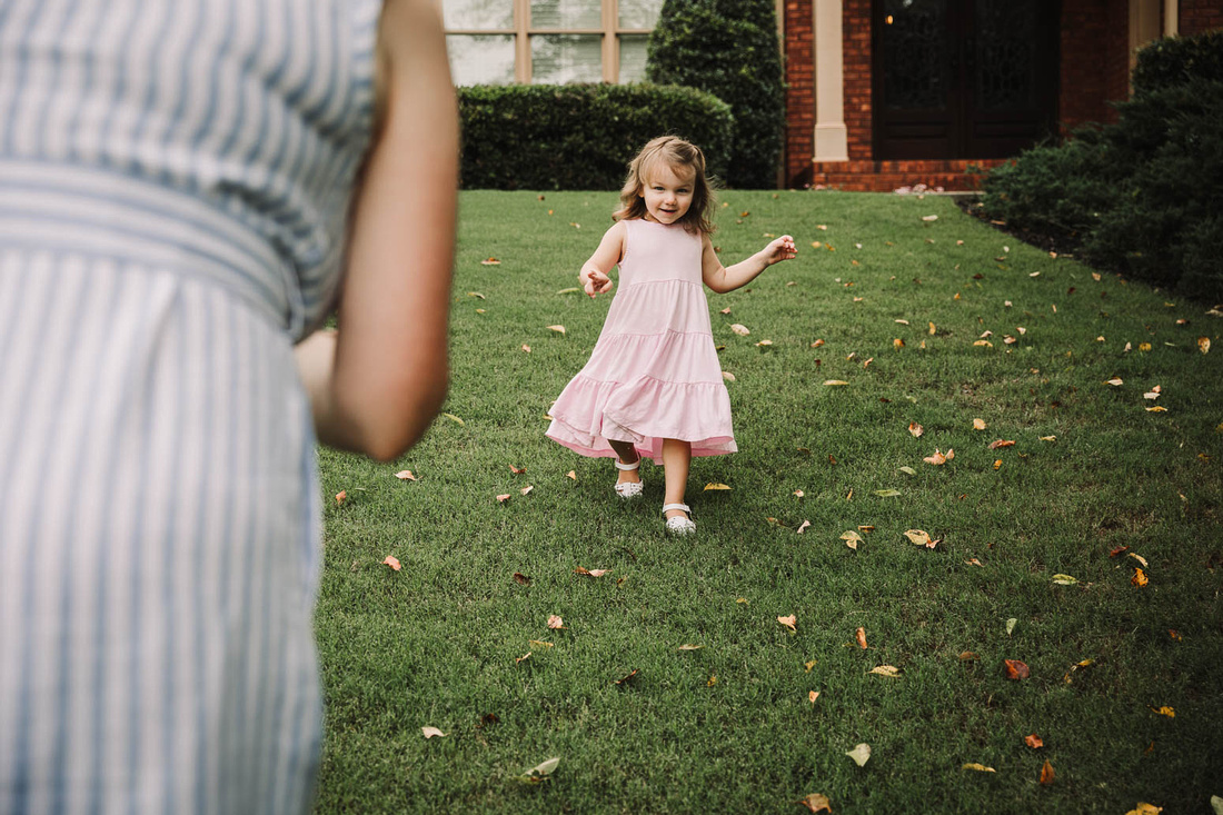 little girl runs to her mother outside their home
