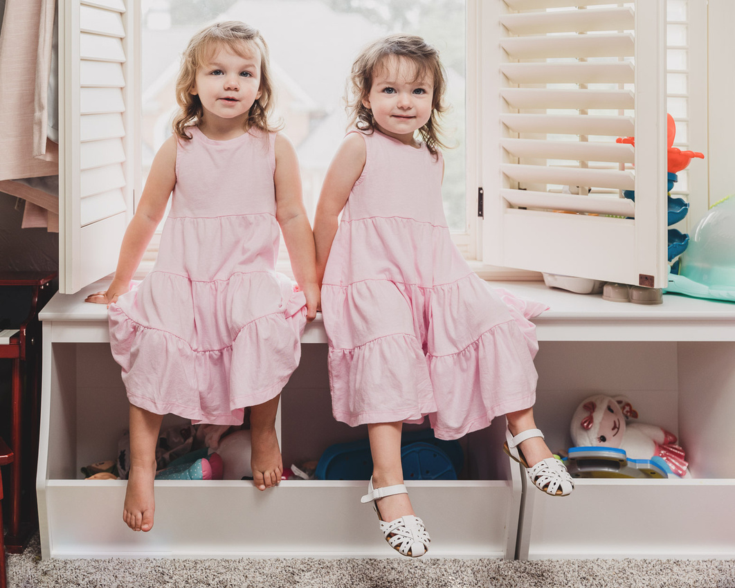 two little girls sitting on the furniture in their room by monica carlson