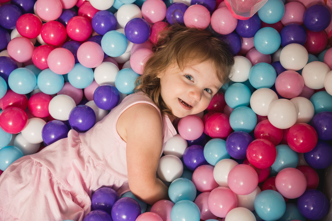 happy little girl looks up at photographer while laying in a ball pit