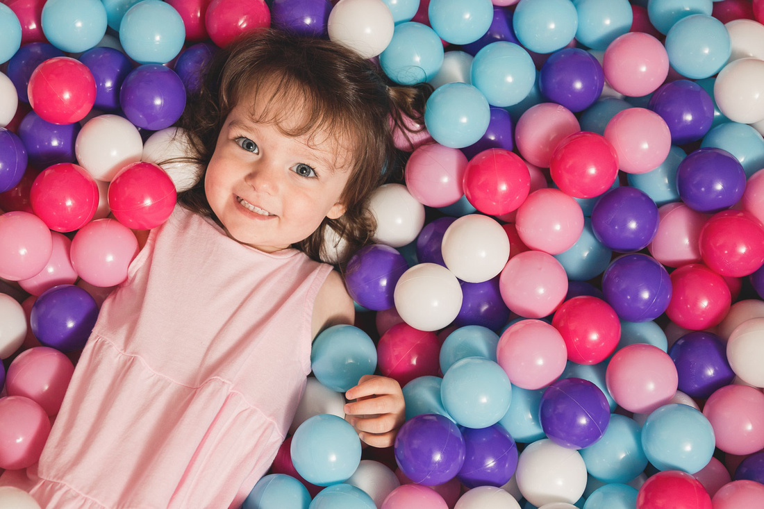 happy toddler girl looks up from a ball pit she is laying in