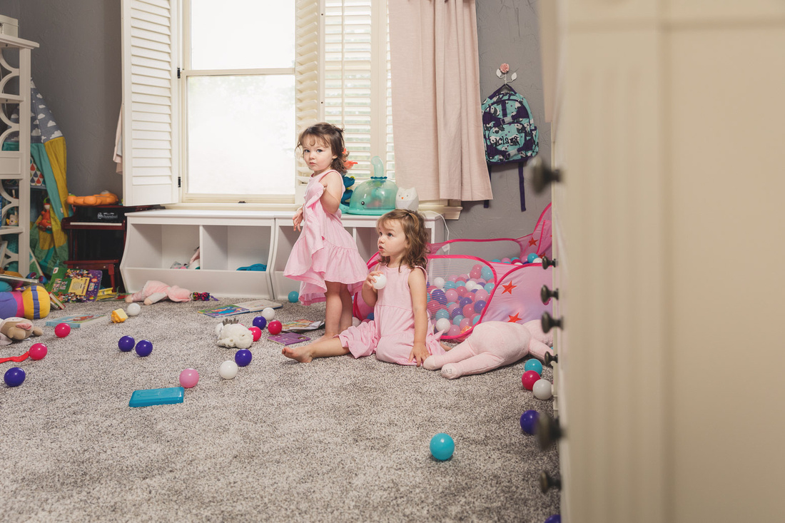 twin girls play on the floor of their messy room during a home photo session
