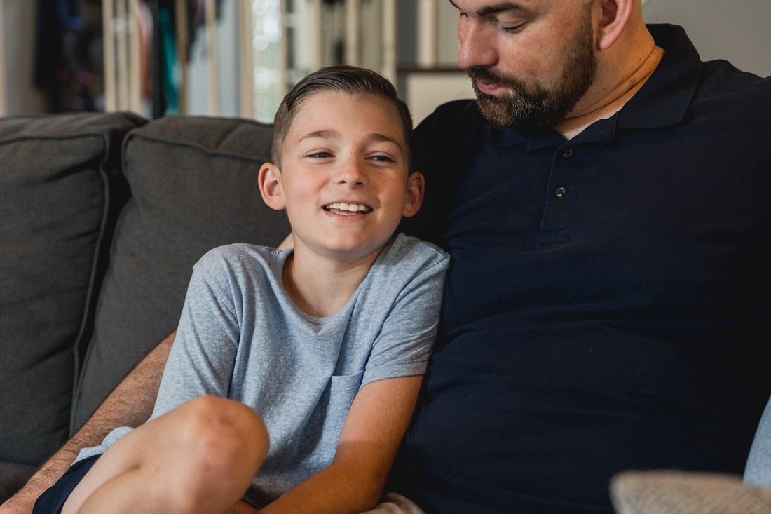 boy giggles while talking to his dad on the couch by monica carlson