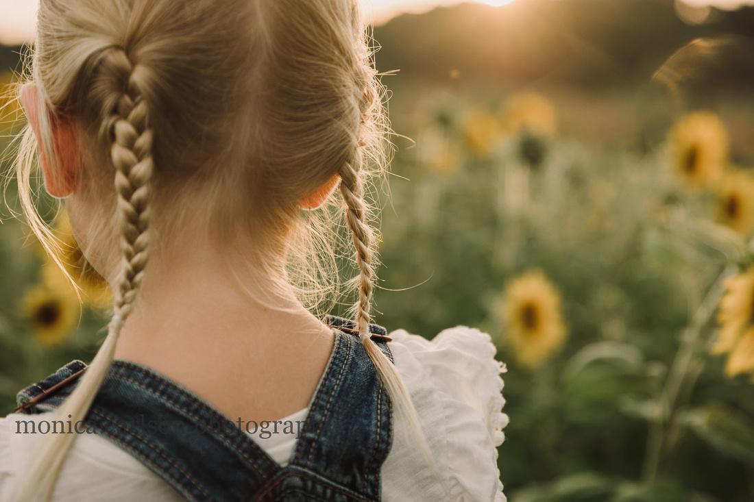 detailed shot of a little blonde girls braids at sunset