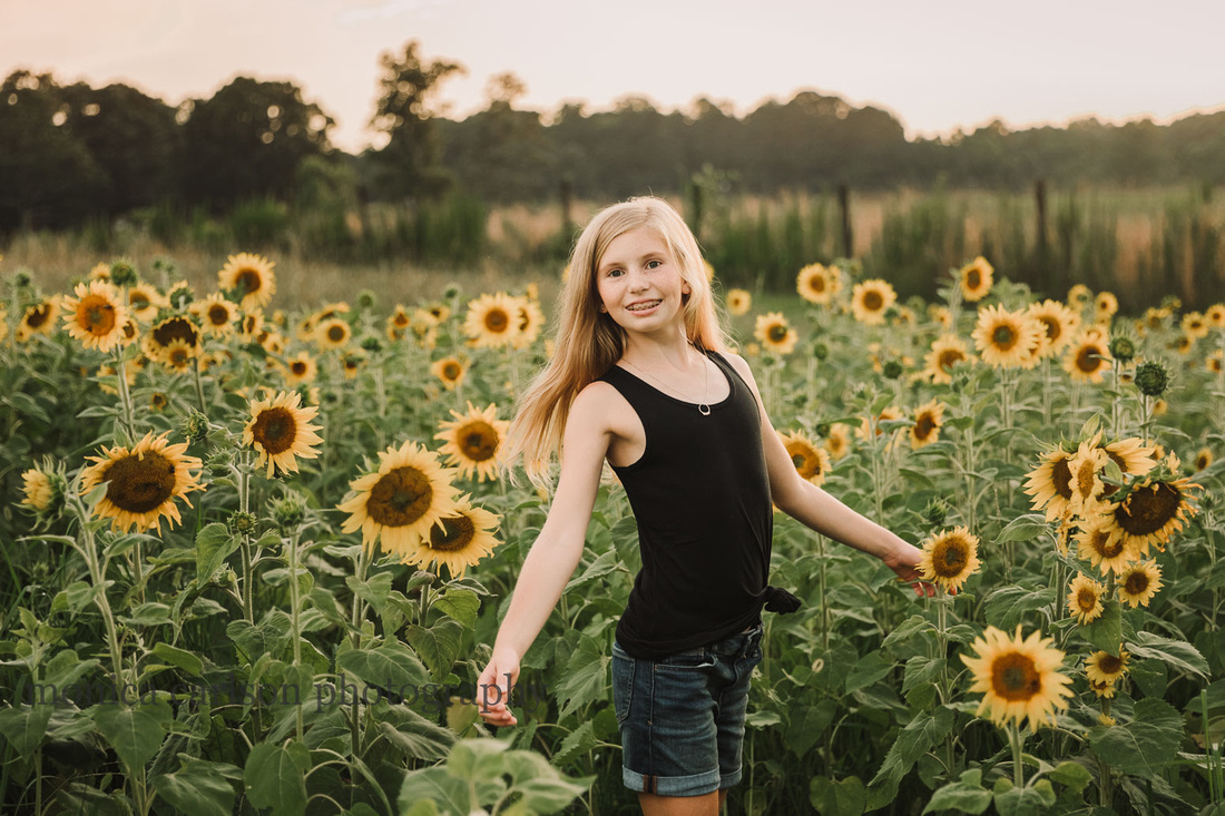 strawberry blonde girl spins on a field of sunflowers