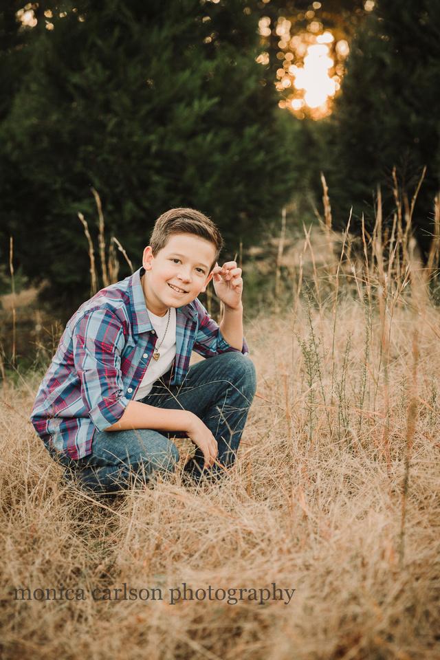 tween boy squats in tall grass at sunset