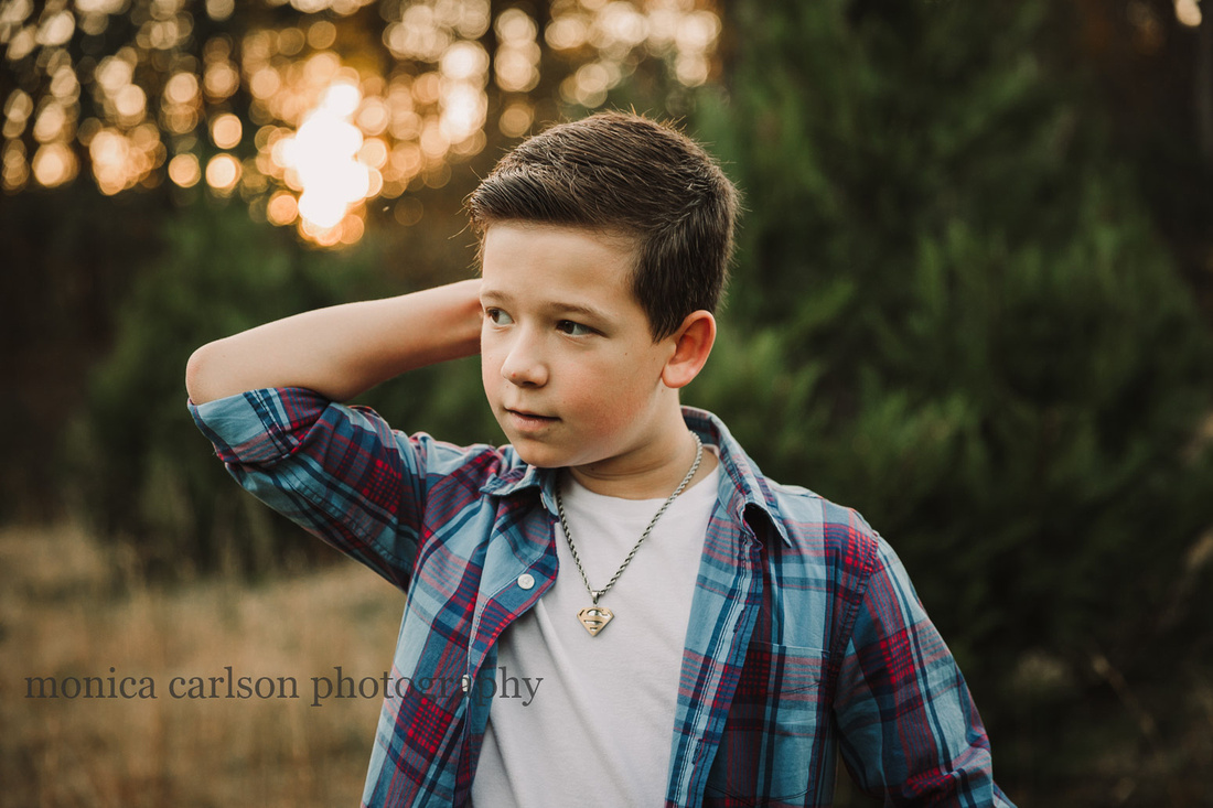 teen boy scratches his head while looking away