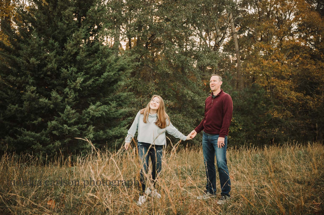 father and teen daughter share a funny moment whill walking along tall grass