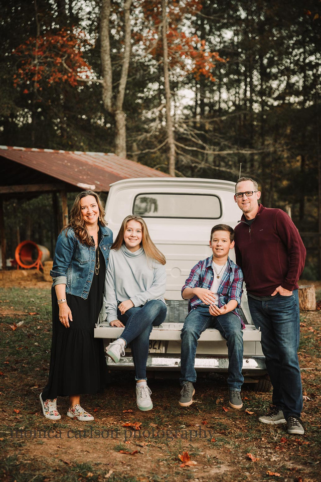 mother, father, son and daughter sit in the bed of a vintage truck in Milton, ga