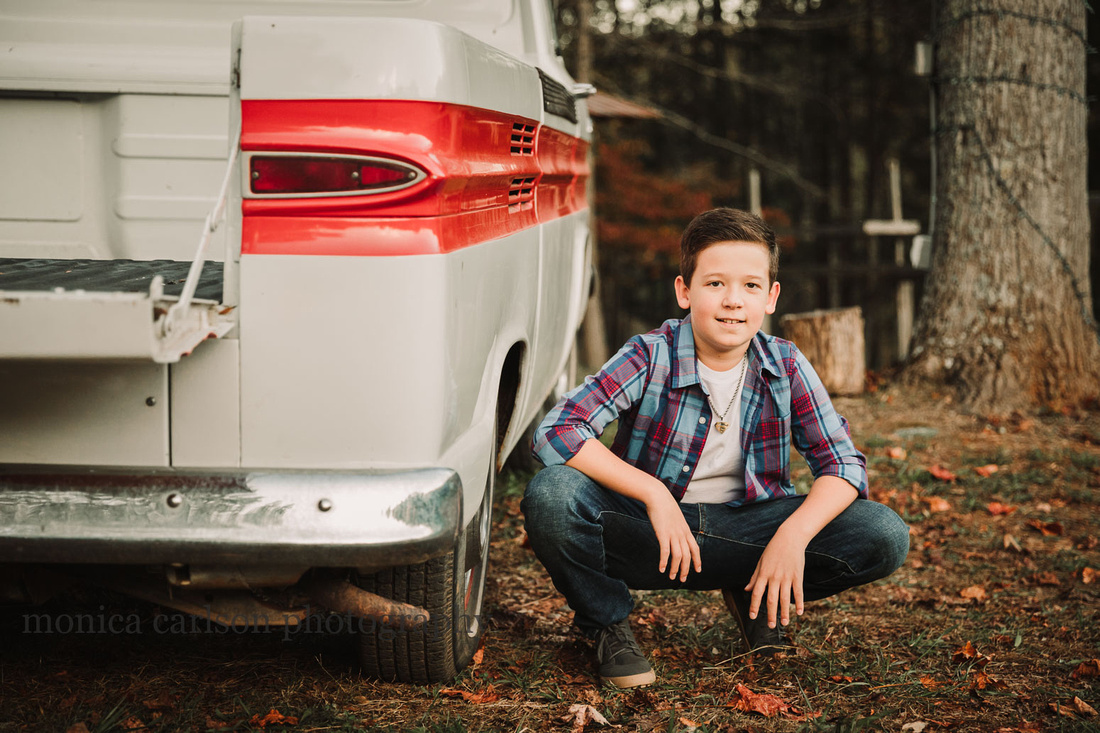 tween boy squats by a vintage truck by monica carlson