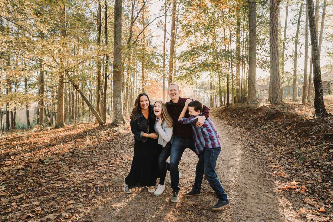 family of four playfully walk along a wooded path in milton, ga during a photo session