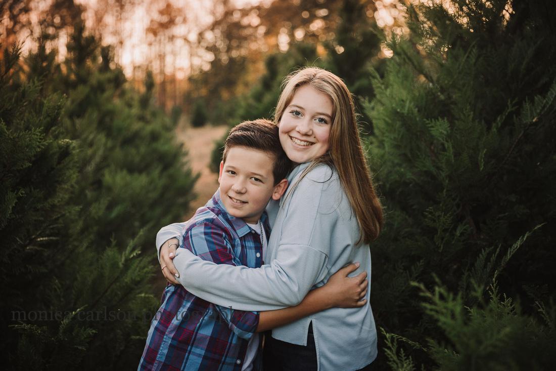 teenage siblings hug while standing among christmas trees at sunset