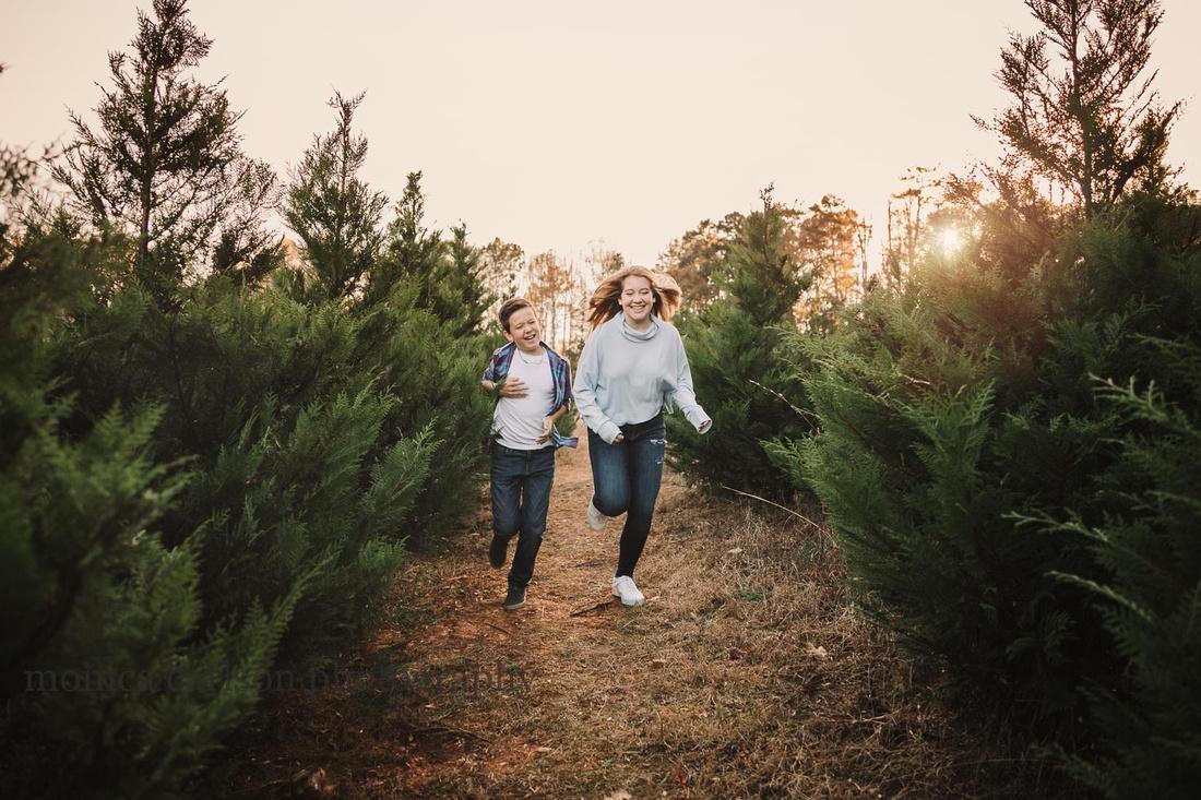teen siblings run through a christmas tree farm