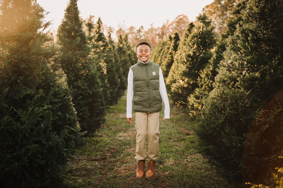 happy tween african american boy jumping up and down between rows of chritsmas trees.