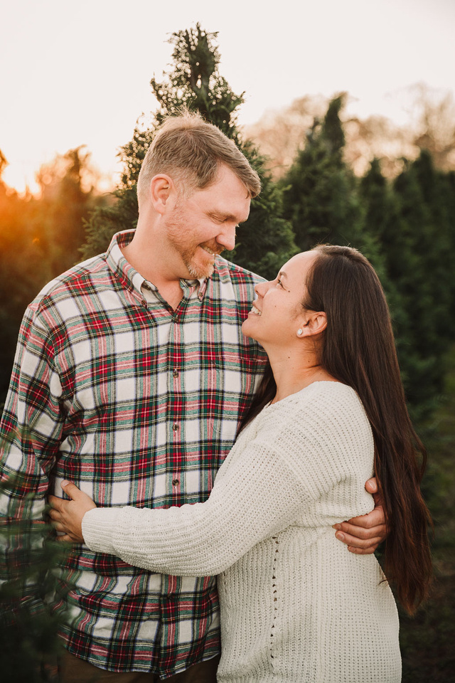 husband and wife look at each other lovingly while at a CHristmas tree farm at sunset