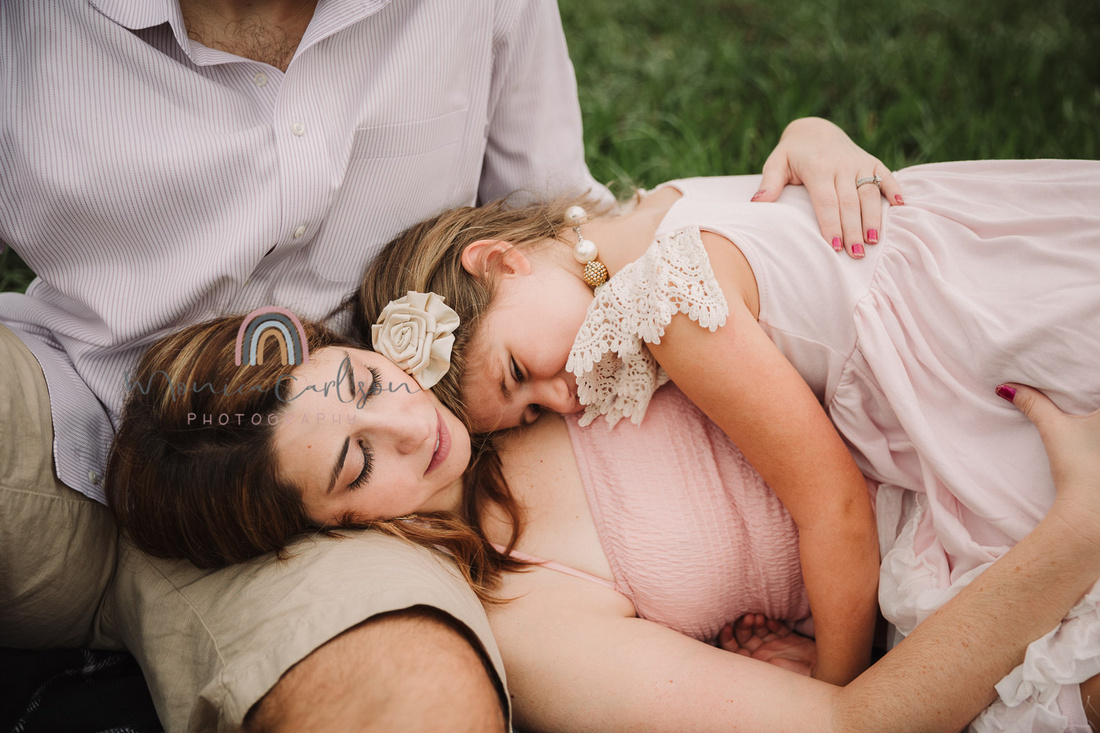 mother lays down on the ground and daughter lays on her chest