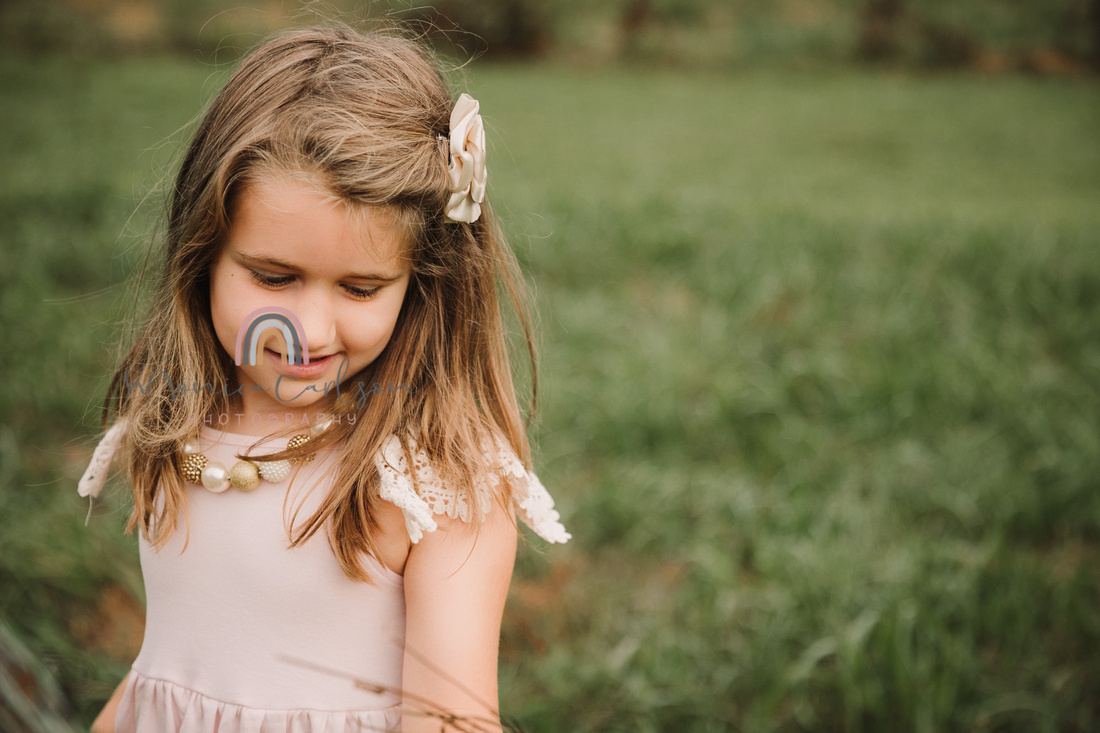 little girl looks whistfully on a green field
