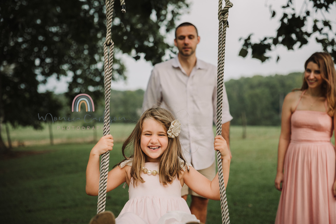 Father pushes his happy girl on a tree swing while mom looks on