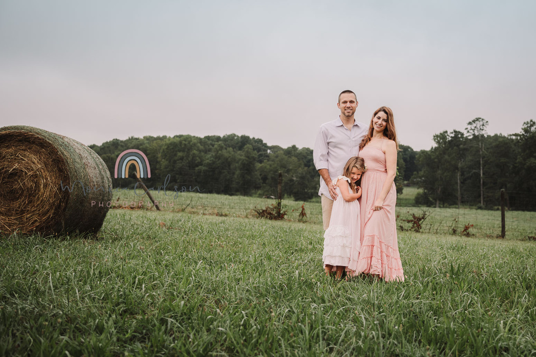 family of three standing on a field at Prospect farms