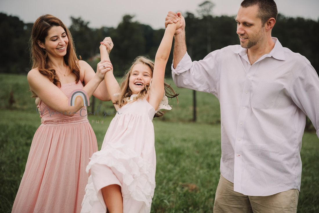 mother and father swing their daughter by her arms
