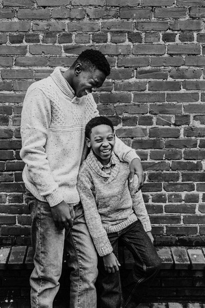african american brothers laughing in front of a brick wall