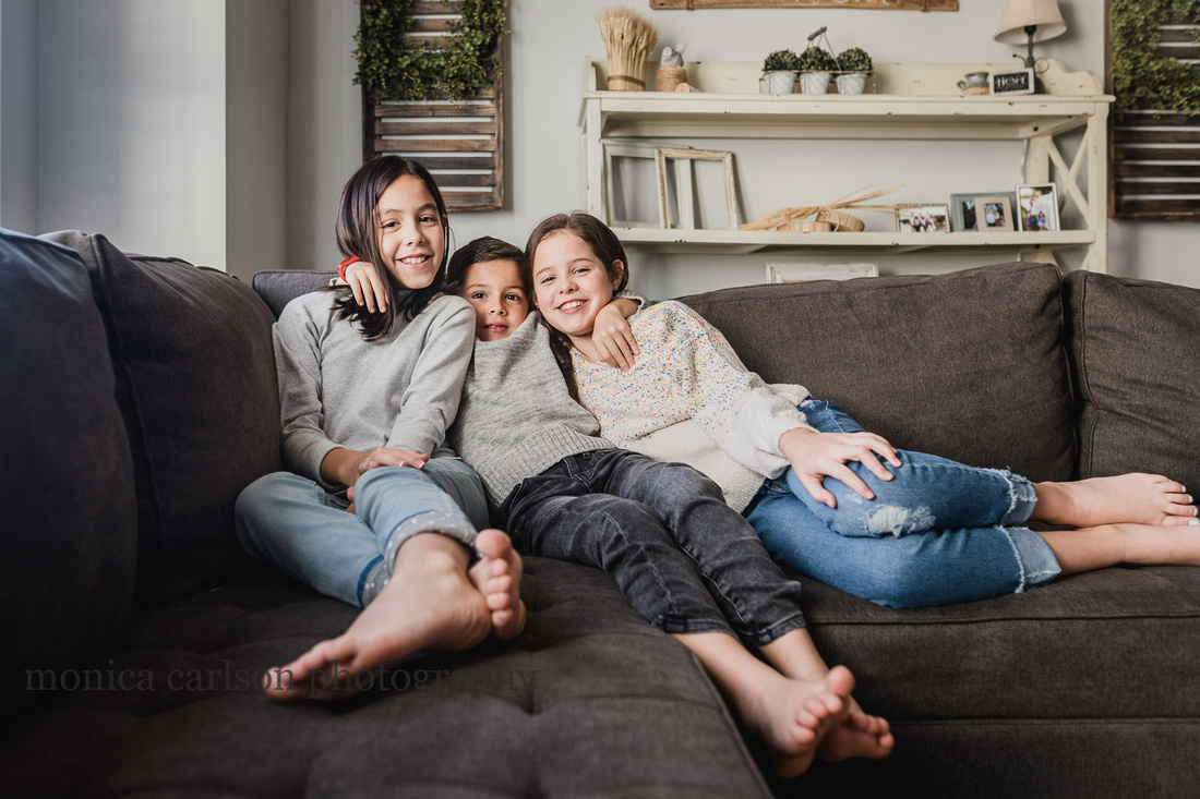 three siblings happily sitting in their living room together during a family photo session