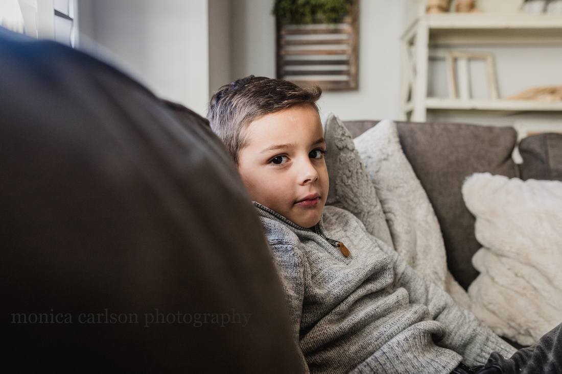 serious portrait of a boy sitting on a couch