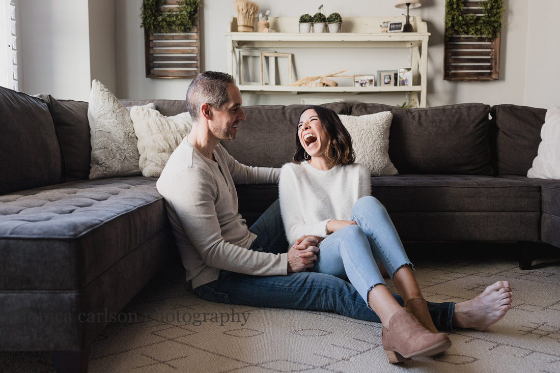 husband and wife laughing together in their living room while sitting on the floor
