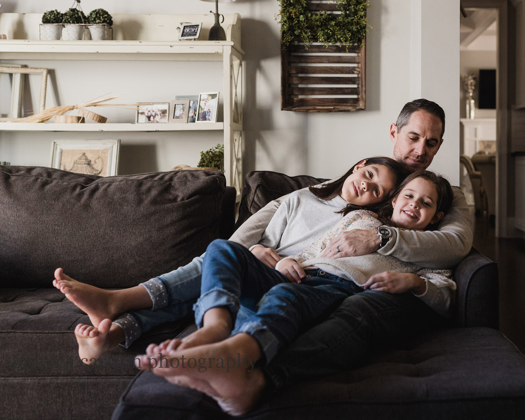 father snuggling his tween daughter on a couch