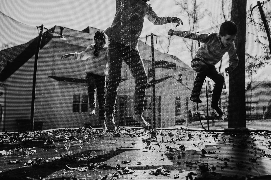 black and white photo of three siblings jumping on a trampoline behind their house by monica carlson