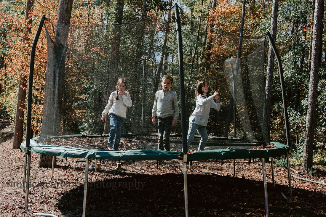 three kids jumping on a home trampoline