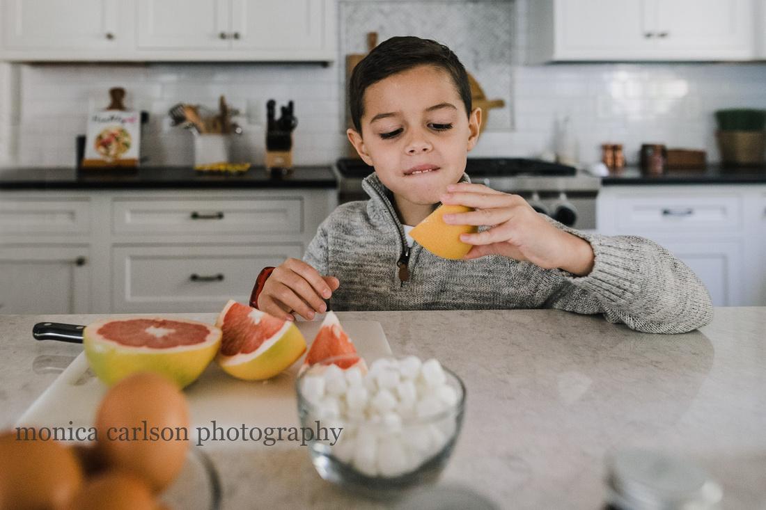 little boy eating a orange