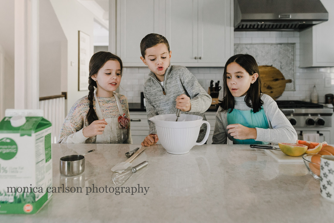 three siblings stirring batter in their kitchen