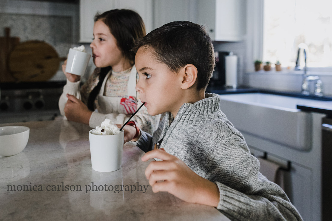 little boy drinking hot chocolate with his sister behind him
