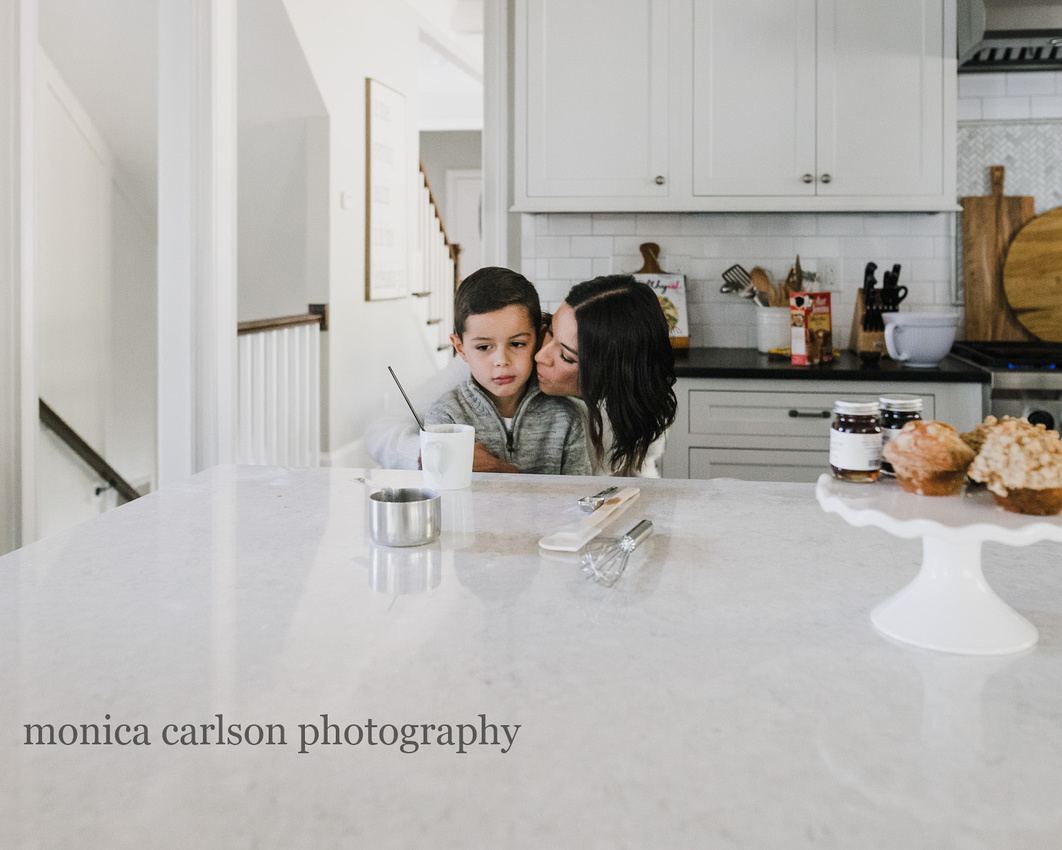 mother kissing her son in the kitchen