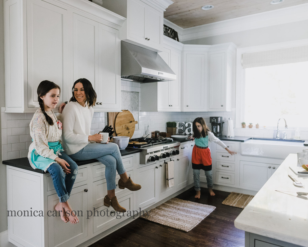 mother and daughter sitting on the kitchen counter while second daughter dances in the background