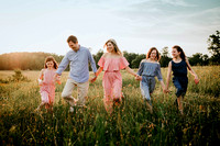 beautiful family walking in a field of flowers during a photo session