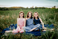 three sisters sitting on a blanket in a wildflower field