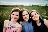 three preteen sisters smiling on a open field