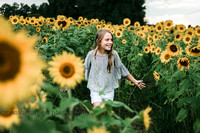 young girl walking in a sunflower field during a mini session with monica carlson