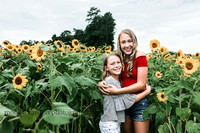 sisters hugging on a field of sunflowers in cumming, ga